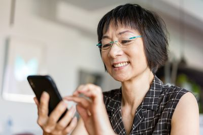 Senior Asian woman using a smartphone.