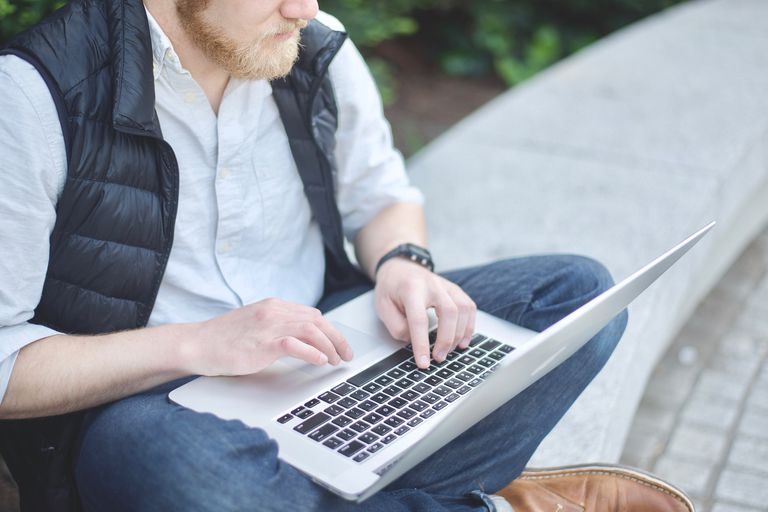 Man sitting down and using laptop outside.