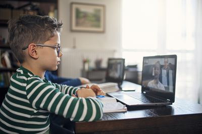 A kid attends online classes from home