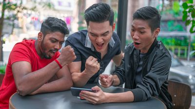 Group of friends playing mobile games on smartphone