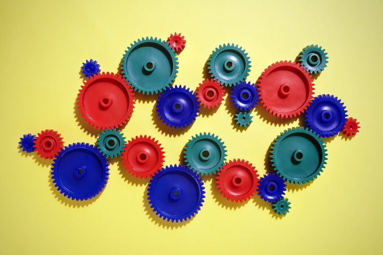 Several colored gears interconnected on a yellow background