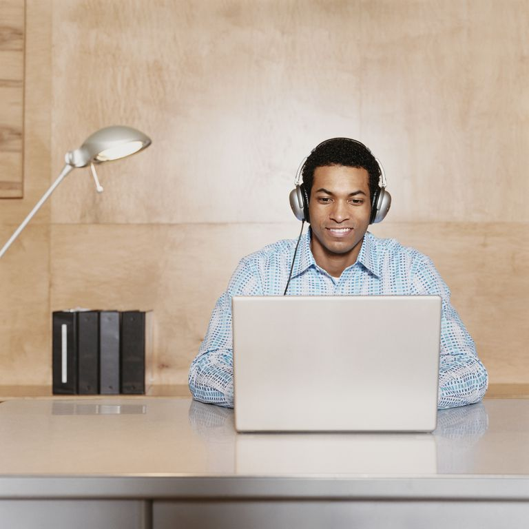 Businessman Wearing Headphones Sits at a Desk Using His Laptop