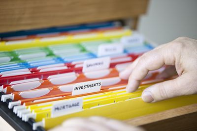 Hands searching through color coded file folders.