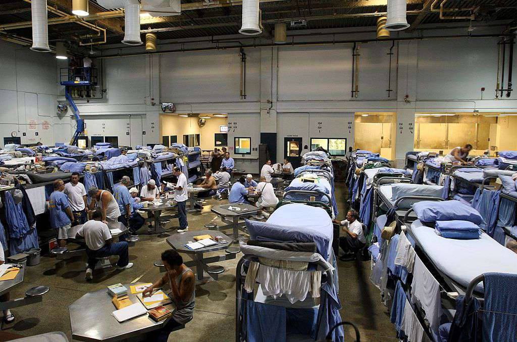 Inmates at the Mule Creek State Prison interact in a gymnasium that was modified to house prisoners