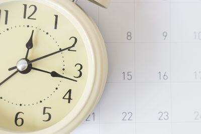Close-Up Of Clock Against Calendar