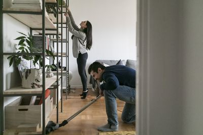 A couple cleaning a living room together
