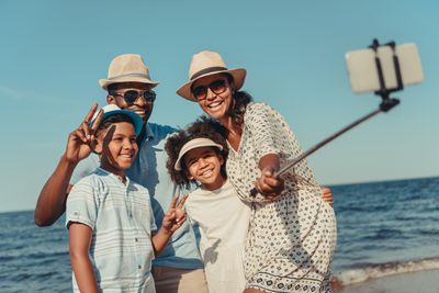 Family at beach taking group photo with selfie stick