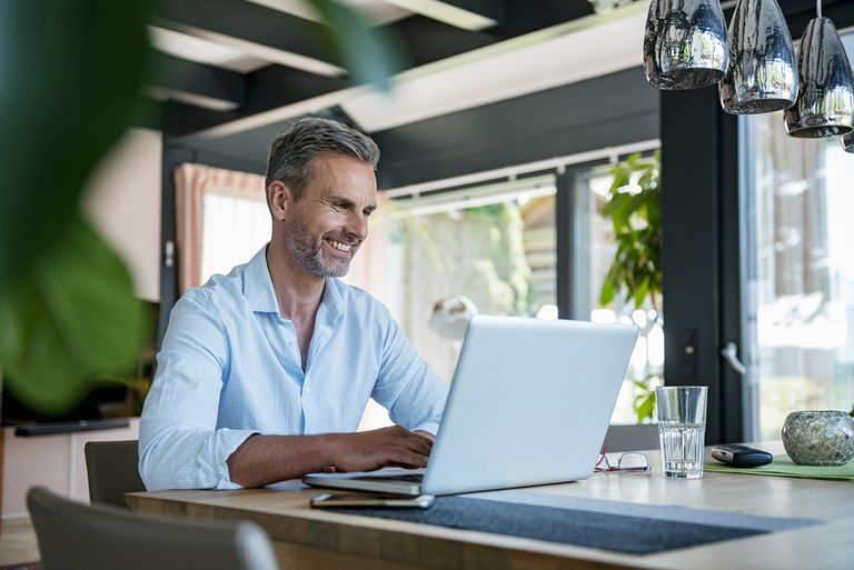 Smiling Man at Home Using a Laptop at Table