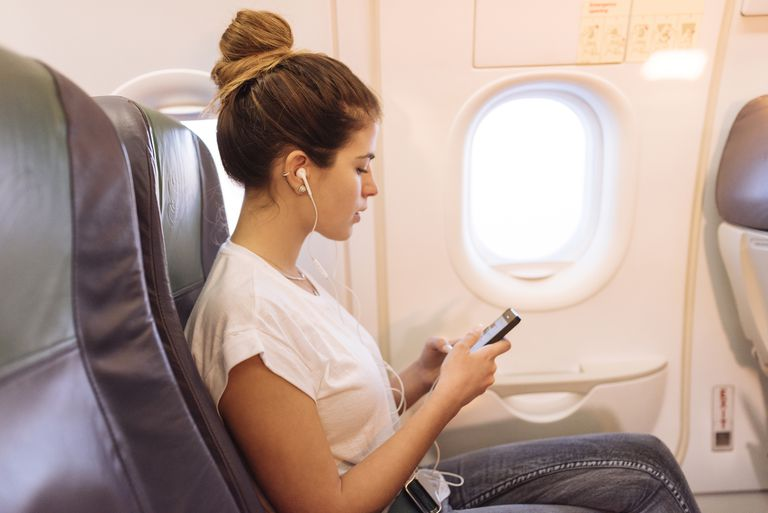 Woman using iPhone in airplane mode while in flight