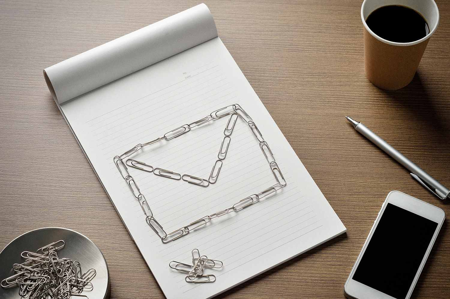 E-mail icon made out of paperclips next to a phone representing email attachments