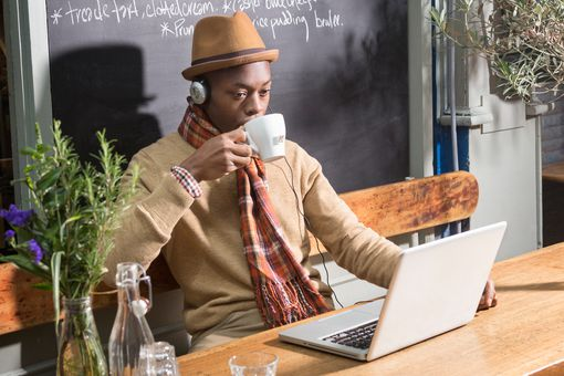 A man in a cafe drinking coffee and using a Windows 10 laptop.