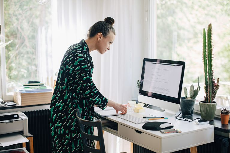 Young businesswoman reading diary while using computer monitor at desk in home office
