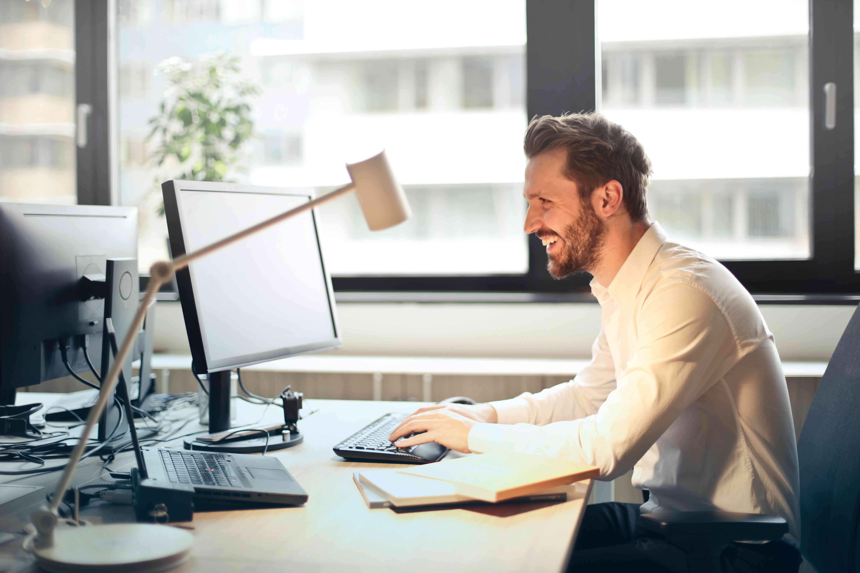 Happy man working on desktop computer