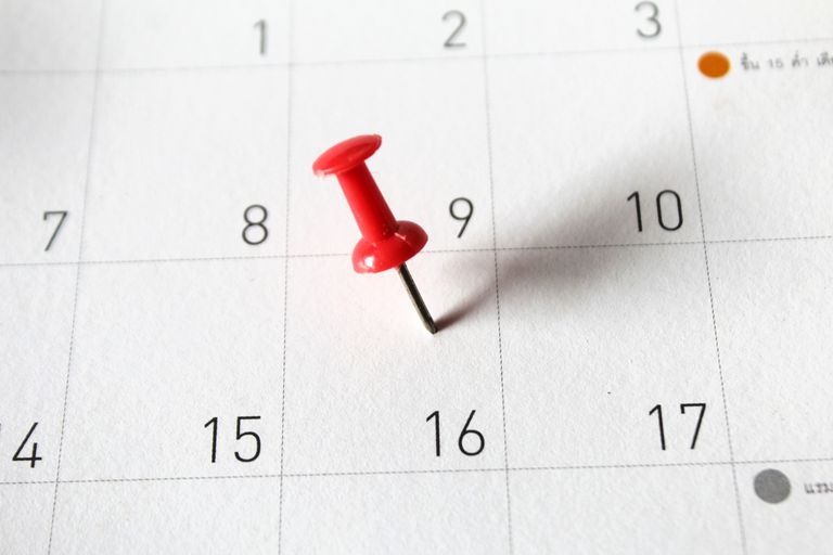 A close-up of thumbtack on calendar.