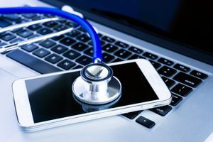 Close up of stethoscope on smartphone screen on an opened laptop
