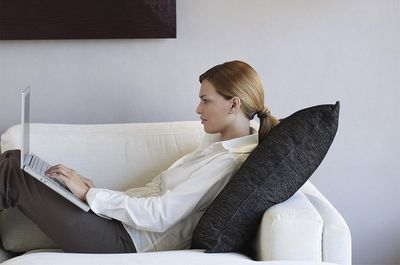 Young businesswoman using laptop in hotel room