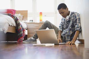Teen boy using computer in room