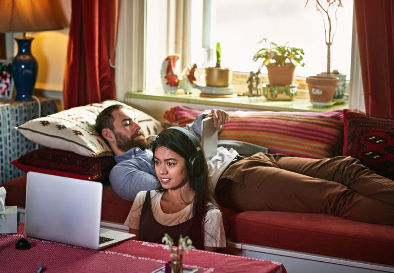 Couple together one with tablet and one watching laptop, sharing an internet connection