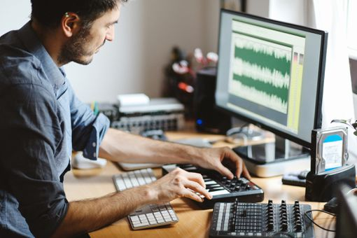 A man at a desk producing music connected to his PC