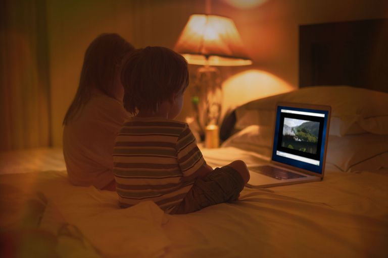 A boy and girl watch a Blu-ray movie on a Windows 10 laptop.