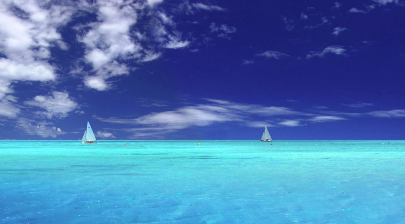Free ocean wallpaper featuring distant white sailboats in a light blue ocean under a blue sky with scattered clouds