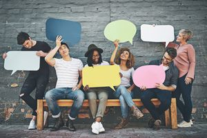 A diverse group of people holding up speech bubbles
