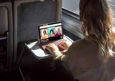 A woman sitting on a train using Apple FaceTime video chat on her Microsoft Surface Pro Windows laptop.