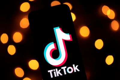 The TikTok logo on a phone with a lighted background