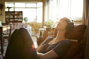 Person relaxing with headphones at home.