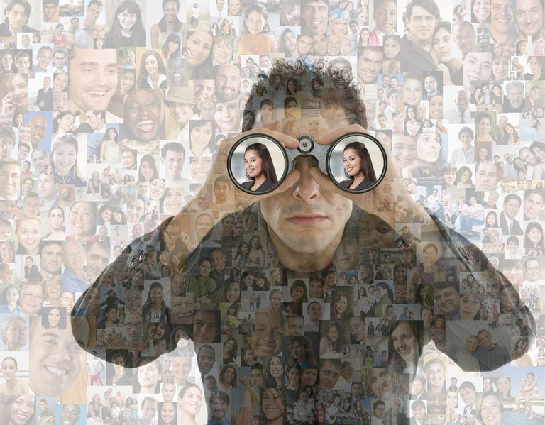 Businessman looking in binoculars over montage of smiling faces, depicting a Facebook stalker