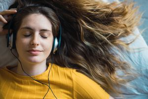 Portrait of smiling person listening music with headphones