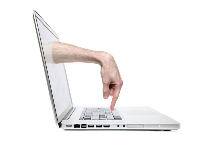 Photo of a hand coming out of a computer screen