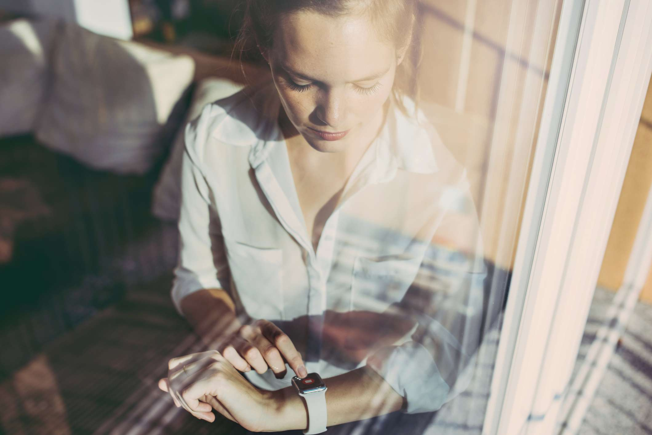 Woman at window looking at smart watch