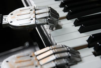 POV shot of robot hands on a piano keyboard