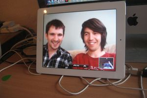 A computer screen showing 2 men and a smaller screen with someone hold a phone.