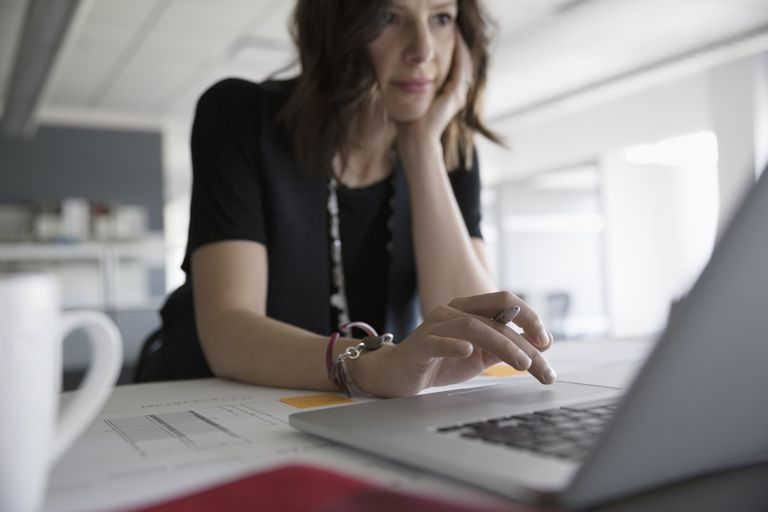 A woman working at laptop in an office.