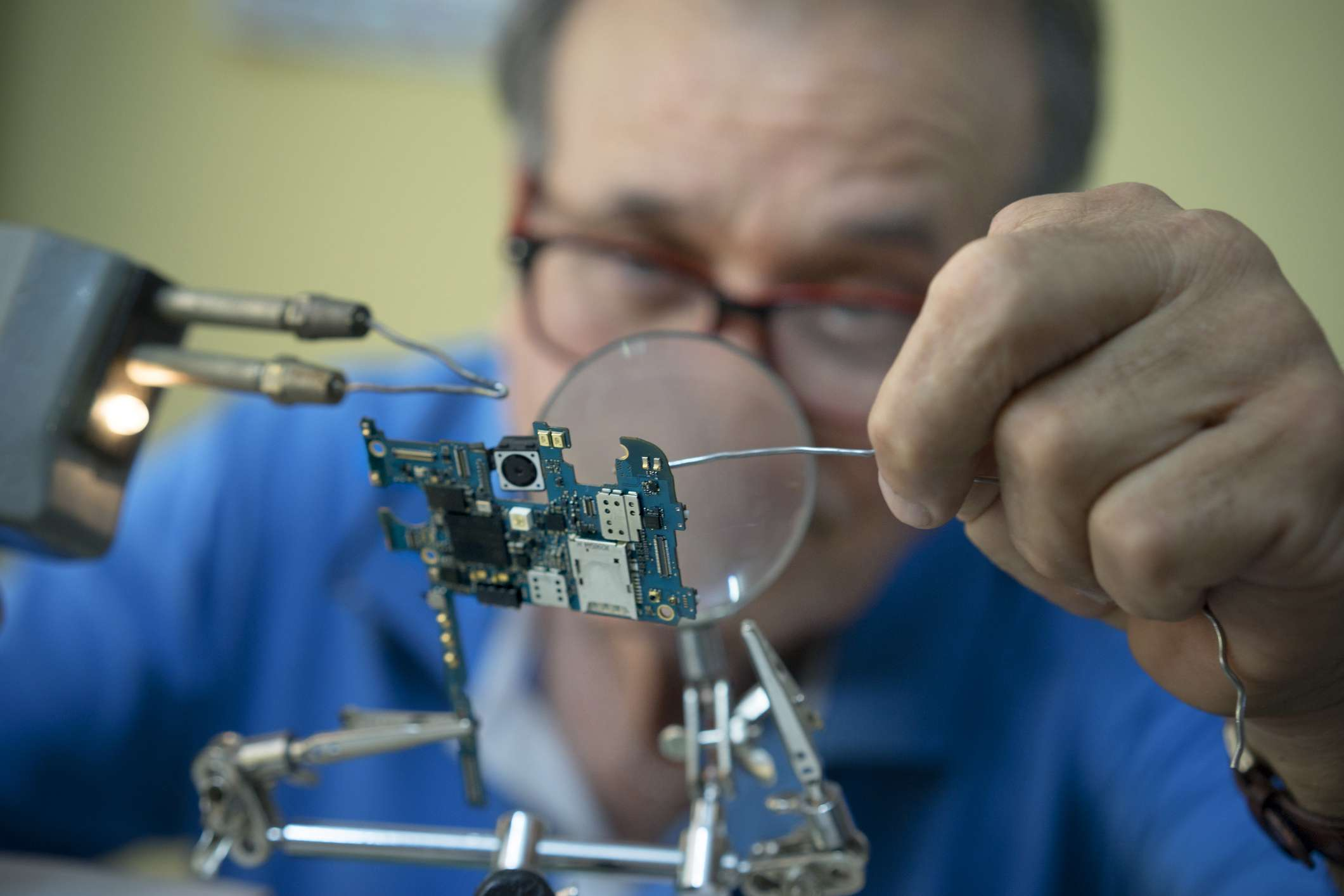 Man welding an electric circuit using a magnifying lens