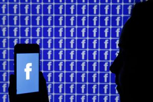 In this photo illustration, the Facebook logo is displayed on the screen of an iPhone in front of a TV screen displaying the Facebook logo on December 26, 2019 in Paris, France.