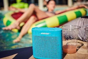 Blue Bose Sounlink next to cups at side of a pool