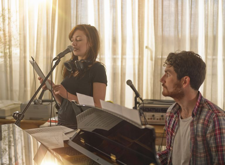 Man at piano, woman singing holding tablet compute