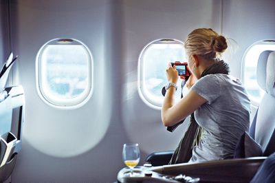 Woman taking a picture with a camera out of the window of an airplane