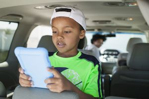 Boy with tablet in minivan teenaged sister driving