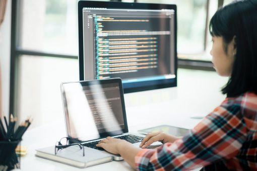 A woman creating code at a computer.
