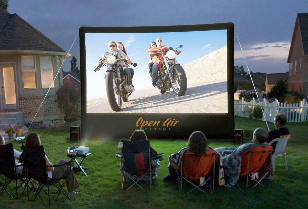People in foldout chairs watching an outdoor inflatable projection screen