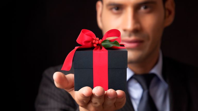 Man wearing a suit and tie giving a Christmas present