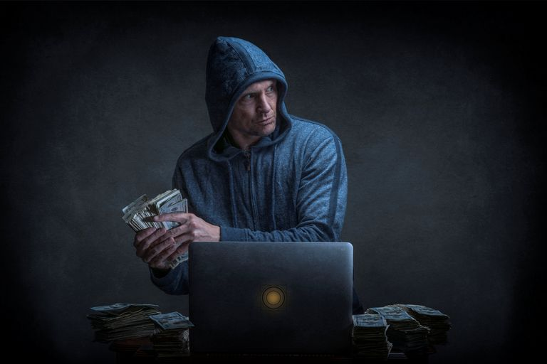 Photo of a man stealing cash next to a laptop computer