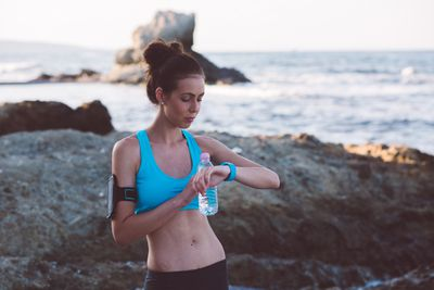 A woman on the beach looking at her fitness band after a workout.