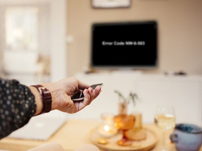 A woman's hand holding a TV remote while pointing it at a TV showing the Netflix error code NW-6-503