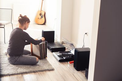 Woman playing vinyl records on turntable with speakers
