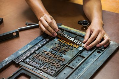 Cropped image of hands fixing letterpress on workbench at workshop